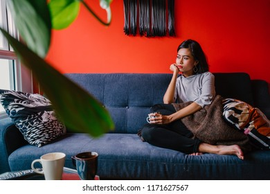 Portrait of a Singaporean Malay woman sitting on a comfortable blue couch in a trendy living room during the daytime. She is relaxing and chilling out on her own on a weekend.