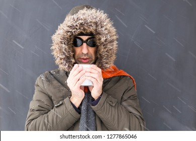 Portrait of a single male winter adventurer wearing a warm green coat with fur hood, an orange scarf and black retro style goggles drinking from a metal cup