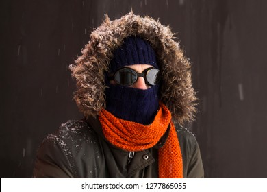 Portrait of a single male winter adventurer wearing a warm green coat with fur hood, a blue ski cap, an orange scarf and black retro style goggles