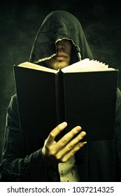 Portrait of sinister cultist in hood with book