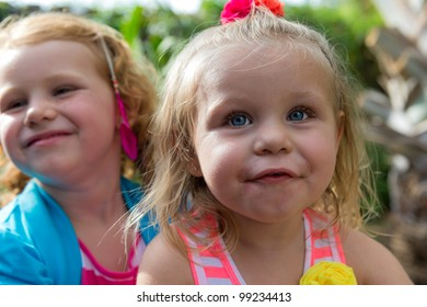 Portrait of sisters playing happy in a backyard, caucasian childs.