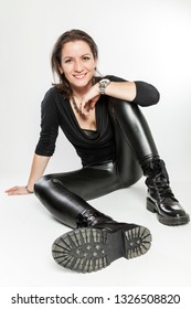 portrait of a sitting brunette woman in the fourties mature female adult relaxing smiling at camera wearing latex leggings boots
