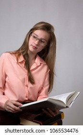 Portrait of a sitting girl with long blonde hair in glasses that keeps on her knees a few books. One of them is uncovered. Closeup. Vertically.