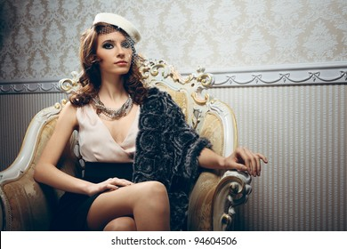 Portrait of sitting pretty young woman in retro style