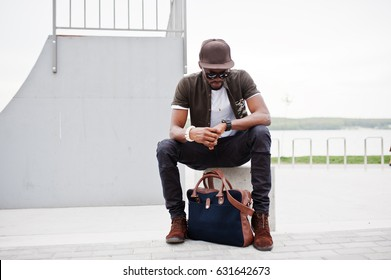 Portrait of sitting stylish african american man wear on sunglasses and cap, looking on his watches outdoor. Street fashion black man.