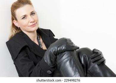 portrait of sitting woman wearing black clothes and boots