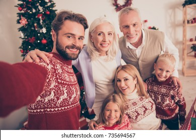 Portrait of six beautiful multi generation relatives, married couples, excited siblings, grandad, granny, in traditional x mas costumes, pine firtree, home, happiness,  hug embrace