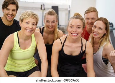 A portrait of six happy, healthy, smiling friends during a yoga class workout exercise.