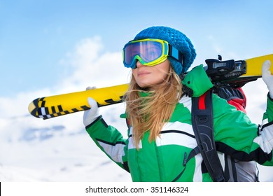 Portrait of skier girl wearing special sportive outfit standing in snowy mountains, looking away, enjoying winter sport, healthy active lifestyle