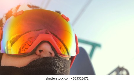 Portrait of Skier in glasses skiing downhill in high mountains on ski lift during sunny day.