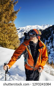Portrait of skier in orange jacket and mask at snow mountain background at sunny day
