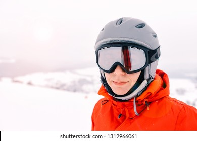 portrait of a skier woman in helmet and ski goggles with foggy mountains background
