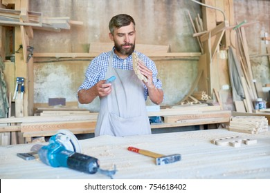 Portrait of skilled bearded carpenter sanding wooden part at table in modern workshop, copy space