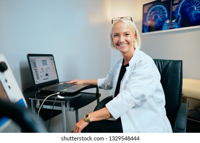 Portrait of skilled doctor working with equipment for brain treatment in hospital. Woman at work with laptop computer in medical clinic, testing and tuning professional machine, smiling at camera