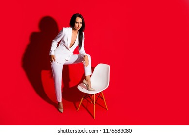 Portrait of skinny confident woman putting leg on chair looking at camera wearing white suit with sexual decollete isolated on vivid red background. Photoshooting studio concept