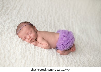 Portrait of a sleeping, 2 week old newborn baby girl wearing frilly, lavender purple bloomers and a pearl headban. Shot in the studio on a white blanket.