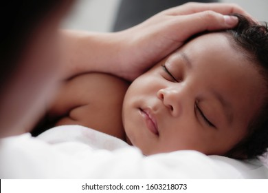 portrait of sleeping african american baby girl with mother