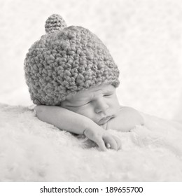 Portrait of a sleeping newborn baby in a knitted hat ( black and white )