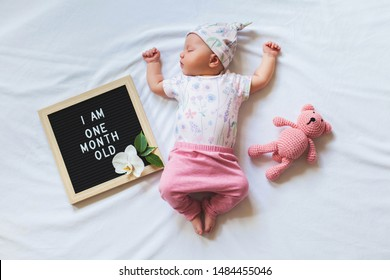 Portrait of sleeping one month old newborn baby girl laying between letter board and teddy bear. Flat lay composition.