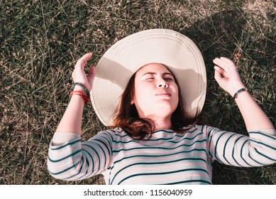 Portrait of a sleeping woman resting on green grass in spring