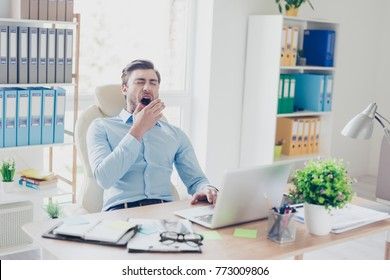 Portrait of sleepy tired agent wearing blue shirt, he is yawning and covering his mouth with a palm, he is sitting in front of computer