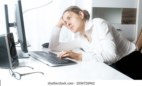 Portrait of sleepy woman looking at computer monitor