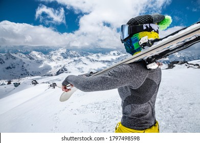 Portrait of a slender skier sportswoman in a cap, mask on her face and ski goggles, mask with skis on her shoulders stands against the background of snow-capped mountains.