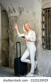 Portrait of a slim, beautiful, confident and elegant Caucasian platinum blond woman in a simple but stylish white outfit smiling as she hails her ride that she booked on her ride hailing app.