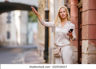 Portrait of a slim, beautiful, confident and elegant Caucasian platinum blond woman in a stylish white outfit smiling as she hails her ride on a street that she booked on her ride hailing app.