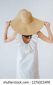 Portrait of a slim brunette girl in big straw floppy sun hat in white dress against white wall background. She's and holding edge of her hat. Turned her back.