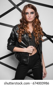 Portrait of slim curly woman in leather jacket posing near the wall