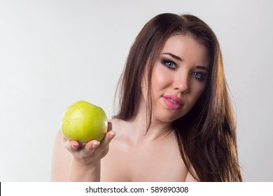 Portrait of a slim girl with an apple on a light background.