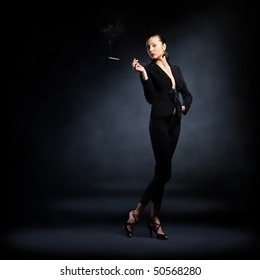 The portrait of a slim young lady in dark clothes holding a lighted cigarette in her hands