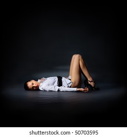 The portrait of a slim young lady in a white shirt lying on the floor