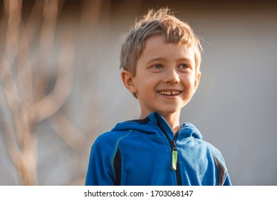 Portrait of the smailing cute 7 years old boy with afternoon sunlight on his face