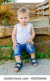 portrait of small angry boy in dirty clothes sitting on wooden plank in the village outdoors.