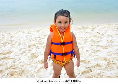 portrait of small Asian young girl ware life jacket on the beach