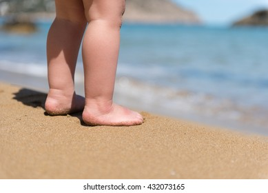Portrait of small baby feet on a sand