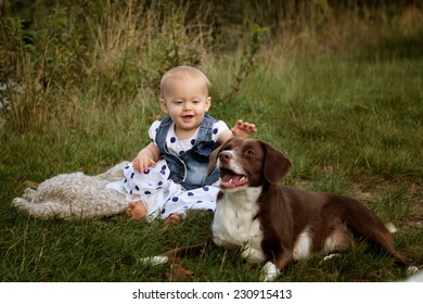 Portrait of a small baby girl at a Lake with her friendly dog pet