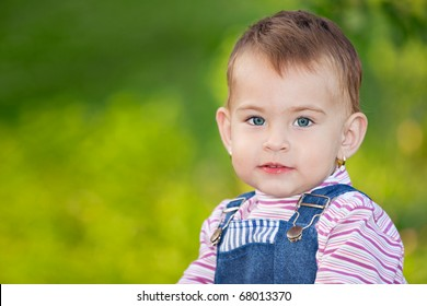 Portrait of a small baby girl wearing jeans, outdoor, looking at the camera.