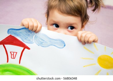 Portrait of small beautiful girl looks out because of children's drawing