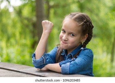 Portrait of a small beautiful girl sitting at a table and threaten with fist.