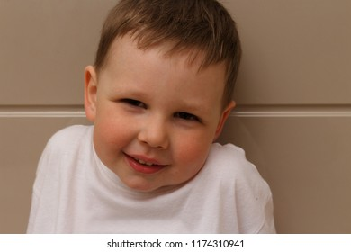 portrait of a small boy, a child in a white T-shirt, looking into the camera with contempt, mistrust and sarcasm. tries to smile, disgust, disdain