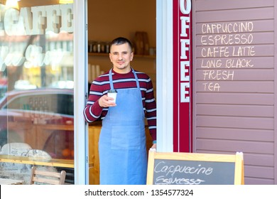 Portrait of small business coffee shop owner smiling and standing in front of shop serving a takeaway coffee – Successful young man working in trendy cafe store holding delicious cup of coffee