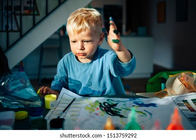 portrait of a small child fingerpainting on table