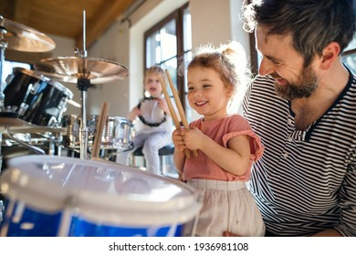 Portrait of small children with father indoors at home, playing drums.