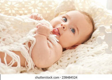 Portrait of small cute girl with blue eyes in her cozy white bed.