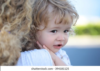 Portrait of small cute serious child boy with blonde curly hair on hands of mother embracing outdoor looking away, horizontal picture