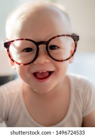 Portrait of the small genius smart and clever adorable baby 1 year old mixed Asian Caucasian wearing spectacles glasses, children education concept