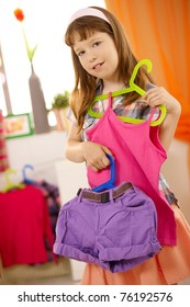Portrait of small girl presenting combination of clothes on hanger, smiling.?
